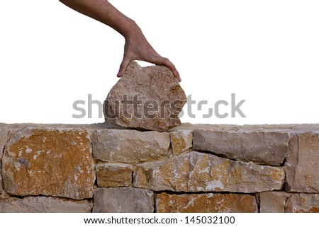 Mason hands working on masonry stone wall stonewall - stock photo