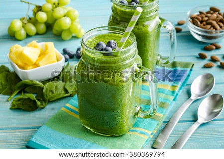 Mason jar mugs filled with green spinach and kale health smoothie with green swirled straw sitting with blue striped napkin and spoons