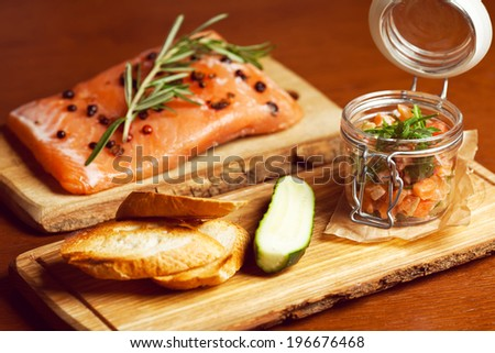 Mason jar with pieces of salmon with fresh cucumber, toasts and ruccola and served with parchment paper on wooden board in restaurant. Vintage style. Close up - stock photo