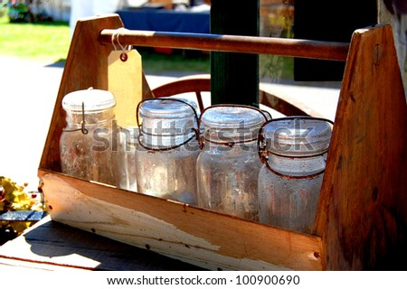 Mason jars covered with water condensation droplets lined up inside a vintage wooden tote box with handle. - stock photo