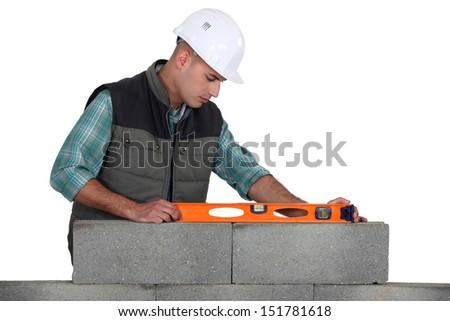 Mason making necessary checks with spirit level - stock photo
