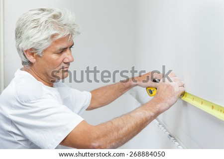 Mason measuring a white wall - stock photo
