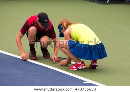 Mason, Ohio - August 13, 2016: Alize Cornet stops play to move a bug off the court in a qualifying match at the Western and Southern Open in Mason, Ohio, on August 13, 2016.