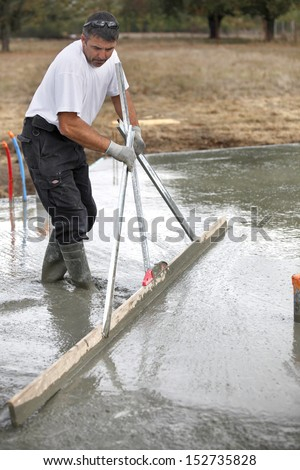 Mason smoothing concrete - stock photo