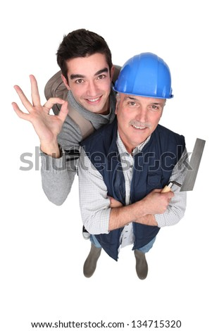 Mason with young apprentice - stock photo