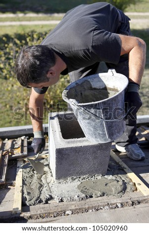 Mason working on building foundations - stock photo