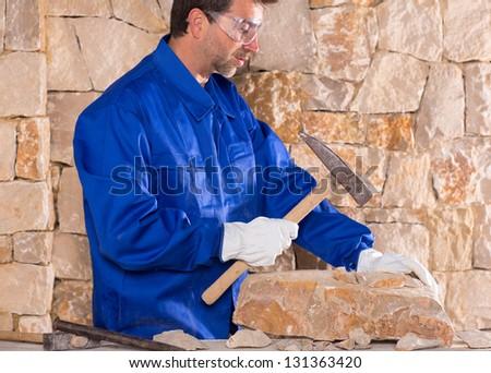 Masonry mason stonecutter man with hammer working on stone wall construction - stock photo