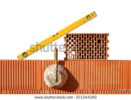 Masonry tools on red brick wall. Bricklaying work. - stock photo