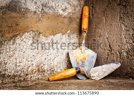 Masonry trowel on an unfinished  concrete wall with space for text - stock photo
