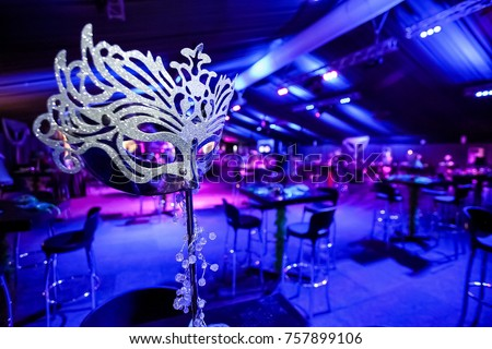 Masquerade Ball Mask Next To A Checkered Dance Floor With Dancers In The Background Blue