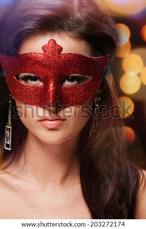Masquerade. Beautiful Girl in a Carnival mask over Holiday Blinking Background. Bokeh - stock photo