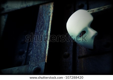 Masquerade - Phantom of the Opera Mask on Rusty Bridge Column - stock photo