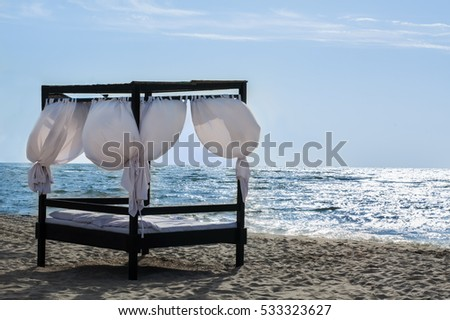 Massage and SPA beds with white linens and curtains on the sea shore