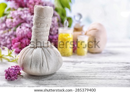 Massage bags with spa treatment and flowers on wooden table, on light background