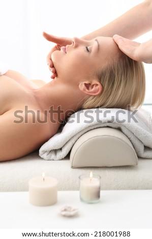 Massage .Beauty salon, the woman at face massage . Attractive blonde woman in spa salon  - stock photo