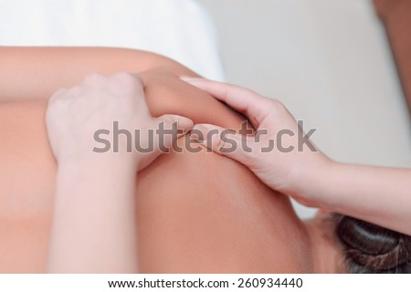 Massage for tired body. Beautiful young woman lying on front and keeping eyes closed while massage therapist massaging her back in spa - stock photo