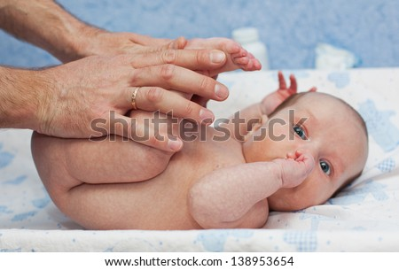 massage newborn baby two months of father's hand focus on hands - stock photo
