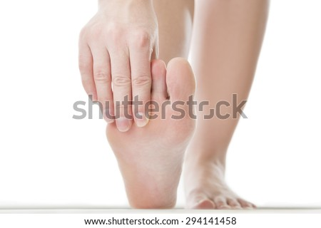 Massage of female feet. Pedicures.Pain in the foot.  Isolated on white background. - stock photo