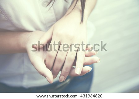 Massage of woman's hand on the white brick wall - stock photo