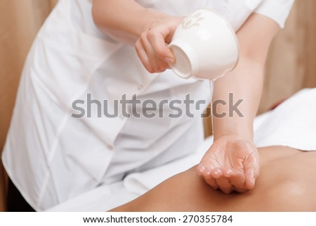Massage oil. Close-up of masseur hands pouring massage oil on the back of a female client