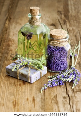 massage oil, herbal soap and bath salt with fresh lavender flowers on wooden background. selective focus - stock photo