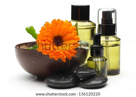 Massage oil,pot marigold flower and zen stones,isolated on white. - stock photo