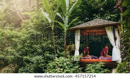 Massage pavilion surrounded by trees with couple receiving body massage. Outdoor spa center at holiday resort. - stock photo