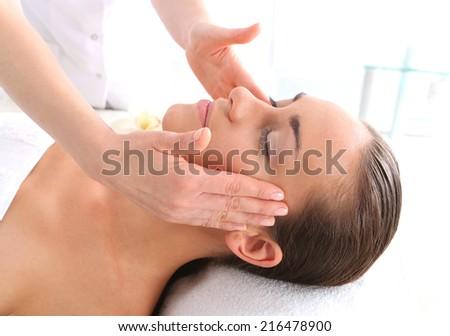 Massage temples.Attractive brunette woman in spa salon. - stock photo