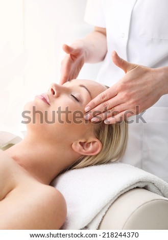 Massage temples.Beautician beautiful woman massaging her temples . Woman in a beauty salon. Masseur massaging a woman in a spa. - stock photo