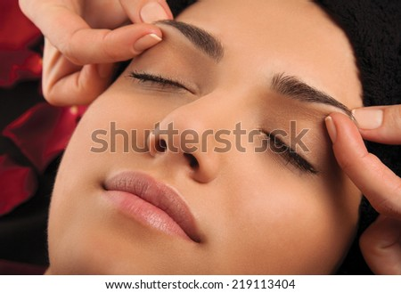Massage the eyebrows of a young woman's face.