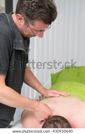 Massage therapist is working with a client - stock photo