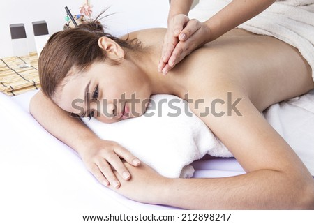 massage therapist's healing hands work on shoulders of woman to relieve stress