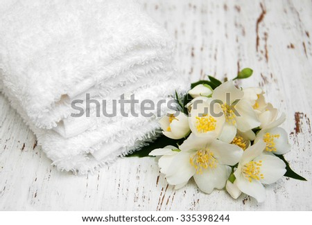 Massage towels and jasmine flowers on a wooden background - stock photo