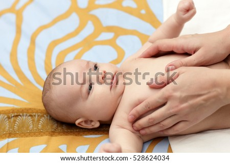 Massaging baby at home in the morning