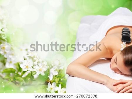 Massaging. Beautiful young woman getting hot stone massage - stock photo