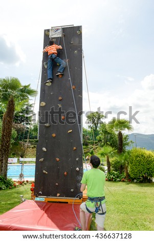 Massagno, Switzerland - 12 June 2016 - Effort of a boy in climbing a wall to reach the top