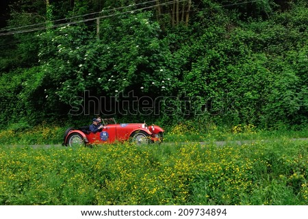 MASSAROSA, ITALY - APRIL 26: A red Aston Martin International takes part to the GP Terre di Canossa classic car race on April 26, 2014 near Massarosa. The car was built in 1929. - stock photo