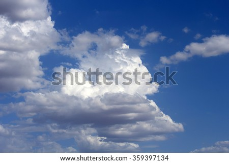 Masses of  majestic white fluffy cumulus  congestus or towering cumulus ice cream  clouds in a blue Australian sky in  summer are a portender of thunderstorm activity  likely to eventuate.