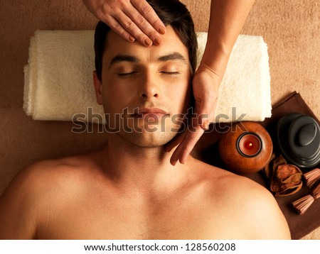 Masseur doing head massage on man in the spa salon. - stock photo