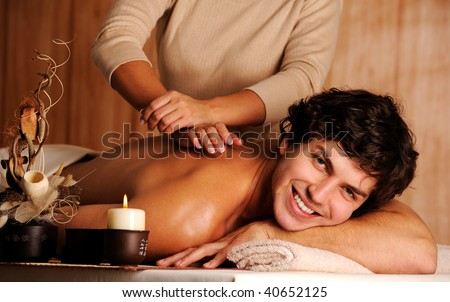 Masseur doing massage a handsome happy young man