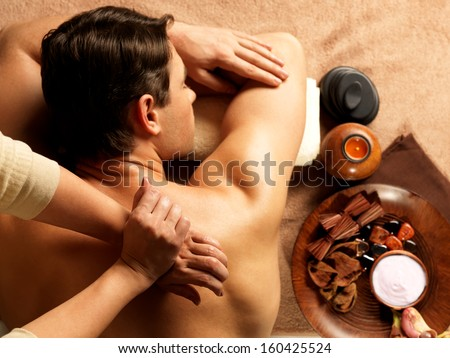 Masseur doing massage of backbone on man body in the spa salon. Beauty treatment concept. - stock photo