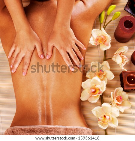 Masseur doing massage on woman back in the spa salon - stock photo