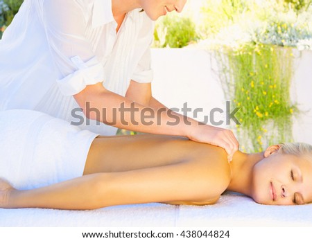 Masseur doing massage on woman body in the spa salon - stock photo