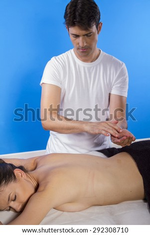 Masseur doing massage on woman body in the spa salon. Beauty treatment concept. - stock photo