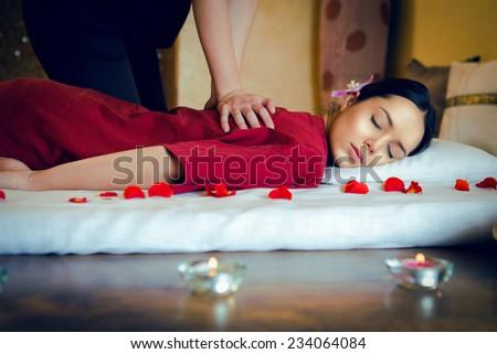 Masseur doing massage on woman body in the spa salon. Bokeh blur.  - stock photo