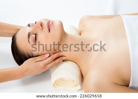 Masseur doing massage on woman face in the spa salon. Beauty treatment concept. - stock photo