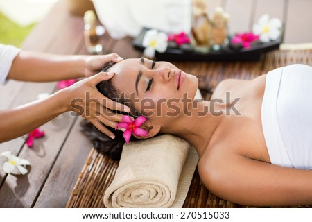 Masseur doing massage the head of an Asian woman in the spa salon