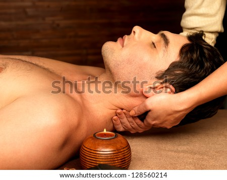Masseur doing neck massage on man in the spa salon. - stock photo