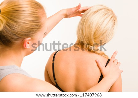 Masseur examining a woman's body, white wall on background - stock photo