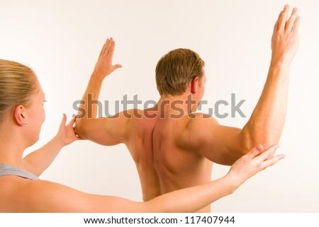 Masseur examining body of men, white wall on background - stock photo
